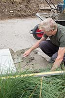 Man adding mortar as base for patio slabs.