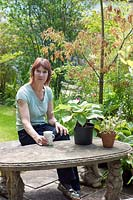 Lorraine Dingwall, sitting at the cast concrete bench and table in the back garden.