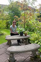 Lorraine Dingwall sitting at the cast concrete bench and table in the back garden.