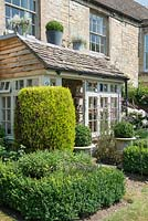 Cottage porch with urns and Buxus parterre and evergreens