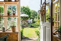 View from inside potting shed to garden where owner is arranging flowers