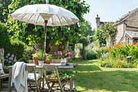 Wooden dining table and chairs with decorative parasol and view to garden