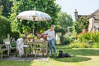 Garden owner arranging cut flowers on table in country garden