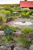 Mixed planting around a circular stone feature in private garden in Scotland.