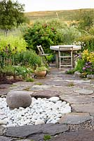 Circular sunken feature with rock and white pebbles, surrounded by patio and seating area in private garden in Scotland.