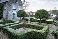 The Courtyard garden with umbrella Portugese laurels, clipped box hedges and a central obelisk at the Old Rectory, Netherbury, UK.