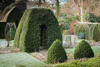 Clipped bay and box, and rose arches over a pebbled path in the garden of the Old Rectory, Netherbury, UK.