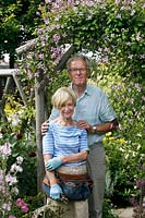 Couple in their garden by flowering climber over a rustic support