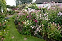 Profusion of pink and white flowers in bed by grass path with stepping stones