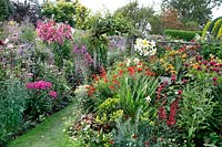 Packed flower beds, in foreground hot theme of red, yellow and purple flowers whilst beyond a bed of pink and purple flowers