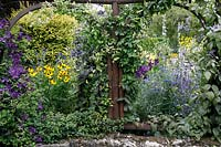 View through the Clematis-covered rustic arches to cottage garden planting beyond