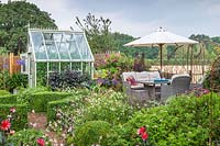 Seating area set amongst flowers with view to countryside, near topiary edging and greenhouse