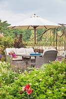 Seating area with lounge garden furniture and parasol, hurdle screen with view of countryside beyond