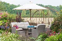 Seating area with lounge garden furniture and parasol, view through woven hurdle to countryside