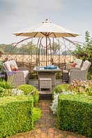 Seating area with lounge garden furniture and parasol, woven hurdle screen with views to countryside