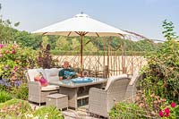 Man sat in lounge furniture under parasol reading, woven screen with views of countryside