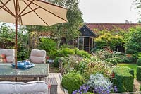 Seating area with lounge garden furniture and parasol, beyond garden with flower beds, topiary and house