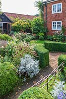 View across central circular paving area with Buxus - Box - hedging, brick path leading to garden studio and to main house with low hurdles at edge of beds