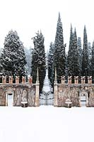 Ornate wall and ironwork gate and avenue of Cupressus - Cypress - trees