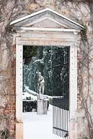 View through open gateway to sculpture in snow covered formal garden
