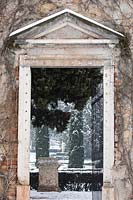 View through gateway in wall to Cupressus - Cypress - trees and statuary beyond