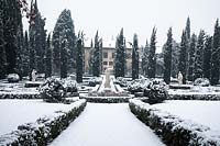 A snow covered French Parterre with stone sculpture
