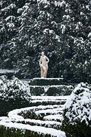 Statue with conifer backdrop with French-style parterre in foreground