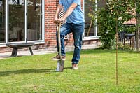 Man using a spade to remove turf where indicated by garden line