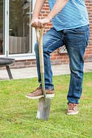 Man using spade to remove turf