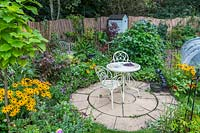 Small circular paved area with ornate white metal furniture set amongst cottage garden style flowers and vegetables