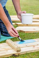 Man using a paintbrush to paint the wood before assembling the picnic bench