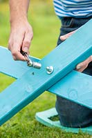 Man using a wrench to tighten nut over washer - assembling picnic bench kit after painting
