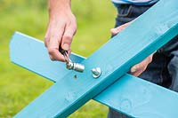 Man using a wrench to tighten nut and washer - assembling picnic bench