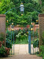 Entrance Court at East Ruston Old Vicarage Gardens, Norfolk, UK with decorative iron work gateway, walls and containers