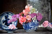 Blue and white ceramic vase with mixed flowers from the garden including Lathyrus, Pelargonium and Spiraea