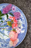Blue and white plate with mixed flowers including Lathyrus, Pelargonium and Spiraea