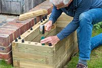 Person building raised bed: hammering dowels into position ready to secure the capping.