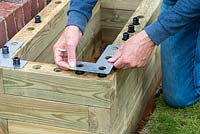 Person building raised bed: fixing an angle plate to each corner for additional stability.