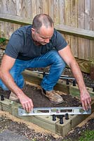 Man building timber raised bed: checking the structure is level with spirit level.