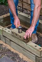 Man building timber raised bed.