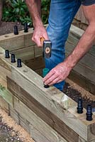 Man building timber raised bed: hammering in plastic dowels that bind timber layers together.