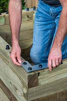 Man building raised bed: fixing an angle plate to each corner for additional stability.
