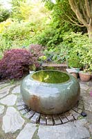 Decorative raised pond amongst colourful summer Acer foliage on shaded patio with seat