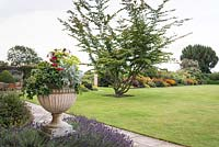 View past planted urn on the terrace to lawn at at Bourton House, Gloucestershire, UK.