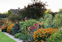 The Warm Border at Bourton House, Moreton-in-Marsh in August including Helenium 'Sahin's Early Flowerer', Dahlia 'Bishop of Llandaff', Kniphofia 'Mango Popsical' and tiger lilies.