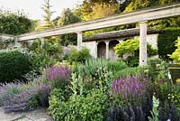 A border below a colonnade, bed full of Salvia, Sedum, Geraniums and Nepeta - Catmint