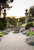 View up wide path at sunset with pools of Nepeta - Catmint - spilling from the double border and a framework of architectural fragments