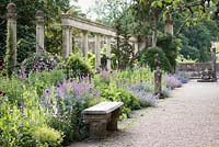 A border full of Papaver - Opium Poppy -  and Nepeta - Catmint - backed by a colonnade and surrounded by sculptural fragments