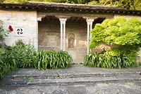 A casita with foliage plants either side of entrance