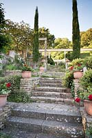 Steps leading up between a pair of Cupressus sempervirens - Pencil Cypress, stone walls on either side with container plantings